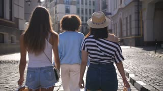 Back view of three multi ethnic female friends walking along shopping street in city in summer and putting paper shopping bags on their shoulders. Asian, mixed race and caucasian girls shopping