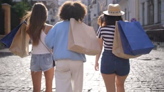 Back view of three young multinational females walking with shopping bags on shoulders on shopping street, turning their heads to camera and smiling happily with beautiful smiles.