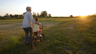 Back view of toddler boy learning to ride a bicycle with grandmother's help. Cute blond grandchild pressing bike pedals while granny holding and keeping him safe. Loving grandmother helping grandson