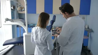Back view of two colleagues in white lab coats at dental office using tablet. Female dentist with male assistant discussing dental diognosis and treatment plan on basis of patient's x-ray shot