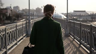 Back view of woman walking away on bridge