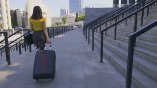 Back view of young adult asian business woman in pencil skirt walking with suitcase to airport. Business lady travelling to the airport on a summer day. Female with luggage going on business travel