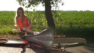 Background teenage girl sitting on road and crying after bicycle accident. Foreground bike seat and spinning wheel. Sad female teen touching her hurting knee and crying from pain.