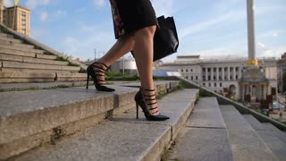 Beautiful businesswoman's legs in high heels stepping down the stairs in city. Executive female with bag in formalwear coming home from work, walking on staircase on cityscape background
