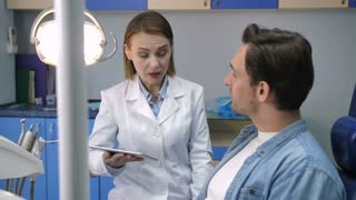 Beautiful female dental doctor in white laboratory coat showing young male patient his dental radiography x-ray shot. Woman dentist discussing diognosis and treatment with young adult man client