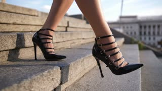 Beautiful female feet in high heeled black retro shoes stepping down the stairs on cityscape background in summer. Attractive slim woman's legs walking down the staircase in city