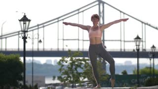 Beautiful mature yogi woman standing in yoga asana, vriksasana, tree pose on city bridge background. Female on one foot, in half lotus position, hands above the head clasped together in anjali mudra.