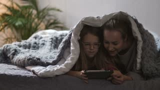 Beautiful mother and daughter using touchpad under blanket in bed together in the evening. Mom and cute teen girl bonding while playing games and watching animation cartoons in domestic interior