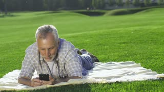 Beautiful senior woman with white hair joining her handsome elderly husband, lying on lawn with smartphone. Positive wife lying near and cuddling with beloved man while both looking at cellphone