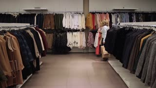 Beautiful shopaholic women buying clothes in store