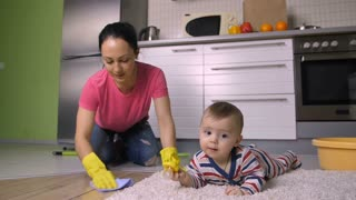 Beautiful smiling mixed race mother on knees washing and scrubbing the floor in rubber gloves. Sweet little baby son playing on the carpet. Young cheerful mom keeping house clean. Slow motion. Dolly