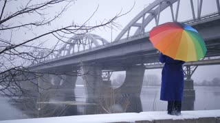 Beautiful view of full length woman standing near city bridge under rainbow umbrella during wind and snowfall. Winter snow healing broken heart, bringing hope and faith in the future