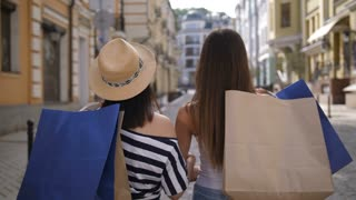 Beautiful young asian and caucasian female shopper friends walking with paper shopping bags on shoulders. Happy positive girls looking at camera and smiling with toothy smiles. Teenagers shopping