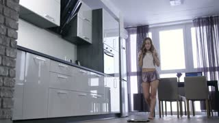 Beautiful young woman checking her weight on body scale in domestic interior and getting upset because of weight gain. Sad slim unhappy female disappointed with weight after holidays
