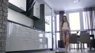 Beautiful young woman standing on body weight scale to measure her weight. Happy blond hair girl jumping off the scale and starts dancing, celebrating weight loss and expressing her happiness at home