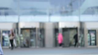 Blur people walking to doorway of shopping mall