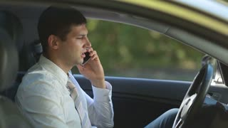 Busy business executive talking on phone in car