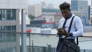 Busy dark-skinned businessman in formalwear text messaging on digital tablet outdoors while leaning on railing over modern citicape background. Serious black executive networking on tablet pc. Slo mo.