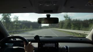 Car driving on straight road on sunny summer day
