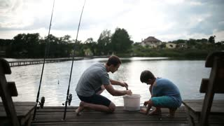 Carefree dad and son preparing to fish on the lake