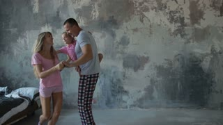 Carefree family with daughter dancing in the room