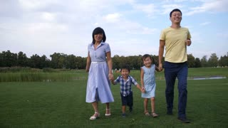 Carefree smiling asian family holding hands and running in park while enjoying leisure together in nature. Cheerful multi ethnic parents with two lovely little kids having fun and running on park lawn