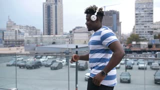 Carefree stylish african american dancer in headphones dancing afrohouse style dance on city street. Positive black male hipster enjoying sound of grooving song and performing afrobeat dance outdoors.