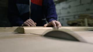Carpenter cutting wooden plank with table saw
