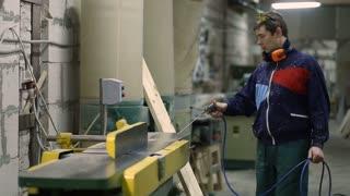 Carpenter using air nozzles gun to clean workplace