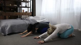 Casual sporty women in upward facing dog position