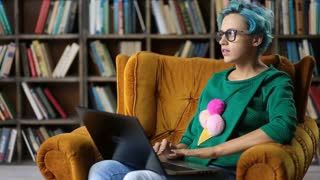 Charming hipster girl typing on laptop in library