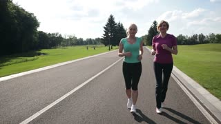 Cheerful adult fit women jogging in the park