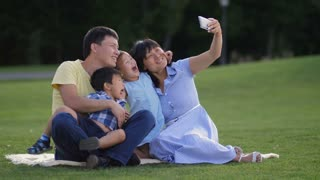 Cheerful asian family with cute little siblings taking a selfie on cellphone in summer park. Beautiful smiling multinational parents and adorable kids showing thumbs up while photographing outdoors.
