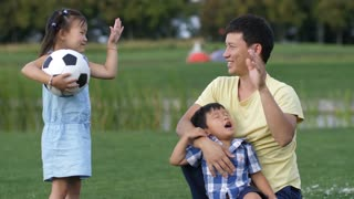Cheerful asian father giving high-five to his lovely preschool daughter in park while family spending great time during weekend. Positive little asian girl with soccer ball giving high five outdoors.
