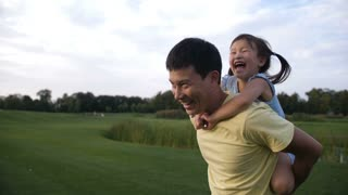 Cheerful asian father giving his cute laughing preschool daughter piggyback ride while having fun in summer park. Adorable little chinese girl enjoying piggyback ride with her smiling dad outdoors.
