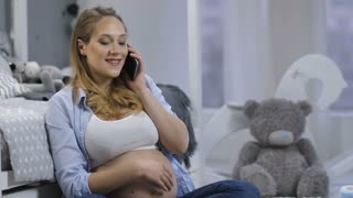 Cheerful beautiful pregnant woman sitting near children's bed talking on cellphone. Young female with big naked belly chatting on mobile phone as baby starts pushing and moving inside pregnant belly