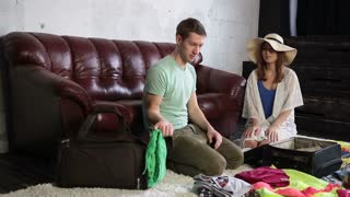 Cheerful couple packing travel bag at home