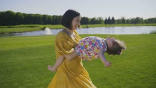 Cheerful joyful mother in yellow summer dress spinning her sweet laughing special needs daughter around on green grass meadow in park. Mom and girl with down syndrome enjoying freetime together