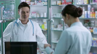 Cheerful male pharmacist reading prescription