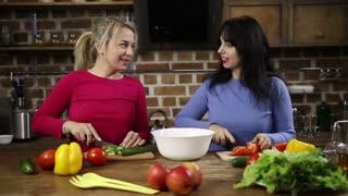 Cheerful women preparing healthy salad in kitchen
