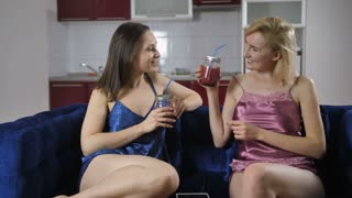 Cheerful young women sitting on sofa in lingerie at home and tasting fresh smoothie. Beautiful females toasting and drinking smoothie. Weight loss, dieting and healthy lifestyle concept. Dolly shot
