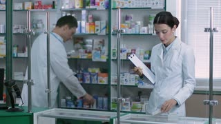 Chemist counting stock with colleague in pharmacy