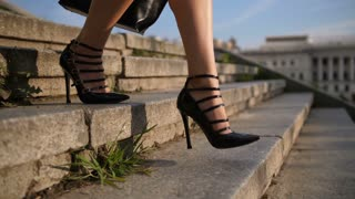 Close-up attractive female feet in high heeled black retro shoes stepping down the stairs in city in the evening. Businesswoman coming back home from work with bag