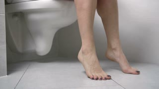 Close-up dolly shot of bare female legs sitting on the toilet in wc and pulling down pink synthetic knickers.