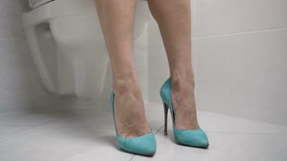 Close-up dolly shot of female legs in high heels, woman sitting on toilet and pulling pink lacy panties down. Girl wearing underwear from synthetic fabrics sitting on toilet in the bathroom