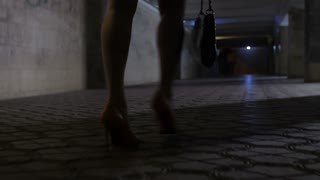 Close-up drunk female legs in high heeled shoes and mini skirt walking alone in dark underpass tunnel at night. Drunken woman stumbling and walking in circles in stiletto shoes