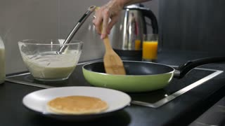 Close-up female hand flipping pancake on frying pan. Woman cooking tasty pancakes for breakfast for family at home.