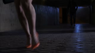Close-up female legs in high heels running away from male attacker in dark subway passage at night. Woman trying to escape strange man following her. Crimininal approachig his victim. Steadicam