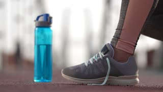 Close-up female runner's feet in sneakers and hands tying shoelaces and taking sport water bottle. Active senior woman running in the morning ties her sports shoes before jogging on bridge. Side view