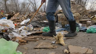Close-up front view of male legs in boots walking at garbage dump site scavenging for plastic and paper to recycle. Homeless man searching for materials at landfill. Steadicam shot